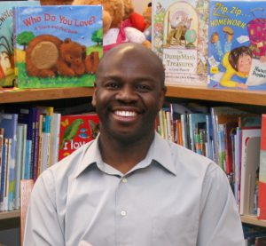 Author, Floyd Stokes, smiling sitting in library